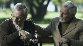 Älterer männlicher tröstender trauriger Freund, sitzend auf Bank, Pflegeheim, Unterstützung stock video