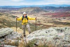 Älterer männlicher Wanderer auf felsiger Klippe Lizenzfreies Stockfoto