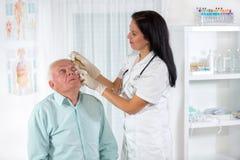 Älterer Mann überprüft von einem Augenarzt stockfotos