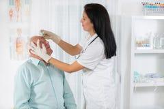 Älterer Mann überprüft von einem Augenarzt lizenzfreies stockbild