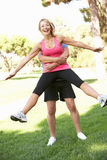 Älterer Mann-anhebende Frau während der Übung im Park Stockfoto