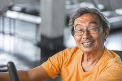 Älterer Mann arbeitet auf Eignungsmaschine für gesundes Konzept des Ältesten aus stockfoto