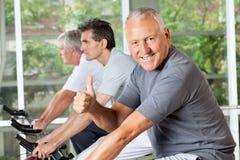 Älterer Mann auf Fahrradholdingdaumen Stockfotos