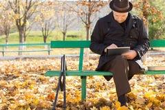 Älterer Mann auf Krücken unter Verwendung eines Tablet-Computers Stockbild