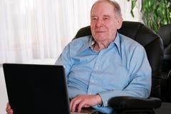 Älterer Mann auf Laptop Stockfoto