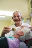 Älterer Mann bei der Arbeit als Herrenfriseur, der Abnehmer rasiert Lizenzfreie Stockfotografie