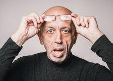 Älterer, älterer Mann in den Gläsern, schauend entsetzt lizenzfreies stockbild