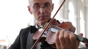 Älterer Mann in den Gläsern spielt auf einer hölzernen Geige zuhause, Porträt stock footage