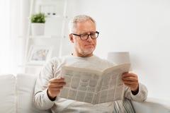 Älterer Mann in den Gläsern Zeitung zu Hause lesend Lizenzfreie Stockbilder