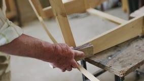 Älterer Mann, den Tischler ein kleines Boot mit seinem errichtet, teilt vom Holz in einer kleinen Werkstatt aus stock video footage