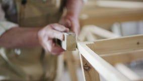 Älterer Mann, den Tischler ein kleines Boot mit seinem errichtet, teilt vom Holz in einer kleinen Werkstatt aus stock footage