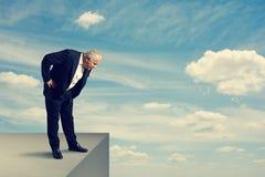 Älterer Mann, der über dem Abgrund steht Stockbilder