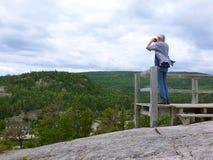 Älterer Mann, der über einer Klippe schaut Lizenzfreie Stockfotos
