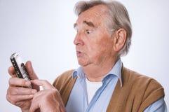 Älterer Mann, der überrascht schaut und sein mobilphone verwendet stockfotografie