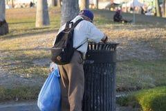 Älterer Mann, der in Abfall gräbt Stockfotografie