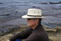 Älterer Mann, der alleine durch Ocean sitzt lizenzfreies stockfoto