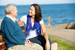 Älterer Mann, der auf Bank mit Tochter sitzt Stockfoto