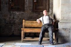 Älterer Mann, der auf der Bank stillsteht Stockfotos
