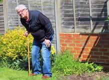 Älterer Mann, der auf dem Aufwecken des Stockes oder des Stocks sich lehnt Stockfotos