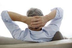 Älterer Mann, der auf dem entspannenden Sofa sitzt stockfoto