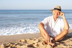 Älterer Mann, der auf dem entspannenden Strand sitzt Lizenzfreie Stockbilder