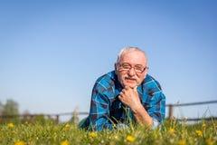 Älterer Mann, der auf dem Sommerfeld im grünen Gras liegt Lizenzfreie Stockbilder
