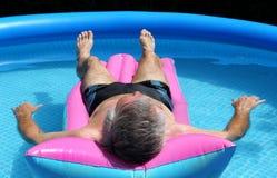 Älterer Mann, der auf ein lilo schwimmt Lizenzfreie Stockfotografie
