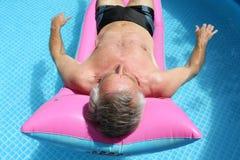 Älterer Mann, der auf ein lilo schwimmt Stockfoto