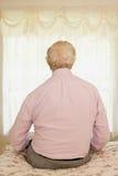 Älterer Mann, der auf einem Bett sitzt Stockbilder