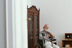 Älterer Mann, der auf einem Rollstuhl sitzt und mit Stock sich stützt lizenzfreies stockfoto