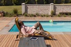Älterer Mann, der auf einem Sonnenruhesessel im Hinterhof schläft stockfotografie