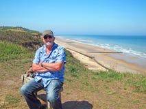 Älterer Mann, der auf einer Bank durch den Ozean sich entspannt Lizenzfreie Stockfotografie