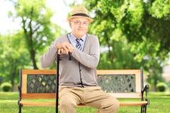 Älterer Mann, der auf einer Holzbank, in einem Park sitzt Lizenzfreie Stockbilder