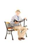 Älterer Mann, der auf einer Holzbank mit einem Buch sitzt Lizenzfreies Stockbild