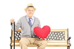 Älterer Mann, der auf einer Holzbank sitzt und ein rotes Herz hält Stockbild