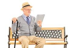 Älterer Mann, der auf einer Holzbank sitzt und von einer Tablette liest Lizenzfreies Stockfoto