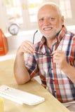 Älterer Mann, der auf Gläser am Schreibtisch sich setzt Stockfotos