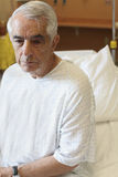 Älterer Mann, der auf Krankenhaus-Bett sitzt Stockbild