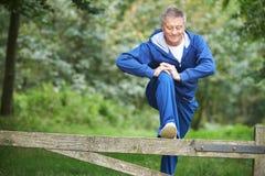 Älterer Mann, der auf Landschafts-Lauf ausdehnt Lizenzfreie Stockbilder