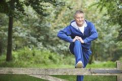 Älterer Mann, der auf Landschafts-Lauf ausdehnt Stockfoto