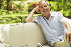 Älterer Mann, der auf Sofa In Backyard sitzt Stockfoto
