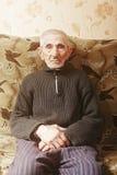 Älterer Mann, der auf Sofa sitzt lizenzfreie stockfotos