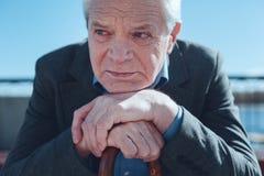 Älterer Mann, der auf Stock sich lehnt und an alte Zeiten denkt stockfoto