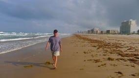 Älterer Mann, der auf Strand geht Stockfoto