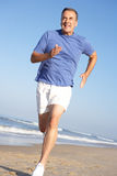 Älterer Mann, der auf Strand trainiert Stockbild