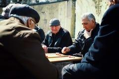 älterer älterer Mann, der Backgammon in einem allgemeinen Park spielt lizenzfreies stockfoto