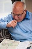 Älterer Mann in der Betrachtung über Karte Stockfotos
