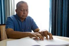 Älterer Mann, der Blindenschrift-Buch im Ruhesitz liest Lizenzfreies Stockfoto