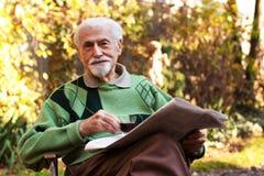 Älterer Mann, der das Papier liest stockbild