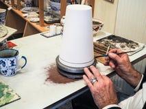 Älterer Mann, der Delft-Porzellan in seiner Werkstatt herstellt stockbild